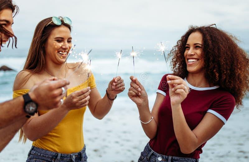 Etniczny grupa ludzi z sparklers przy plażą zdjęcia stock
