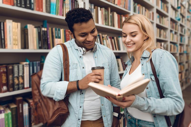 Etniczny hindus mieszał biegowego faceta i białej dziewczyny w bibliotece Ucznie są przyglądający dla książek obrazy royalty free