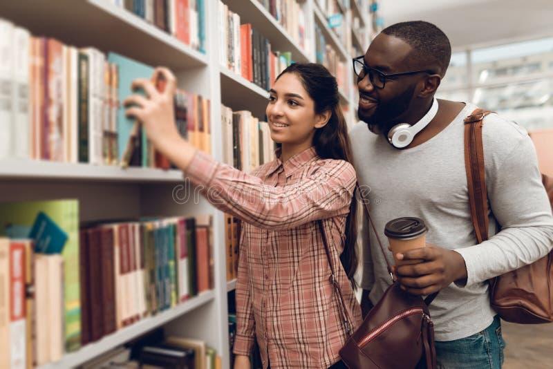 Etniczny hindus mieszał biegowej dziewczyny i czarnego faceta w bibliotece Ucznie są przyglądający dla książek obrazy royalty free