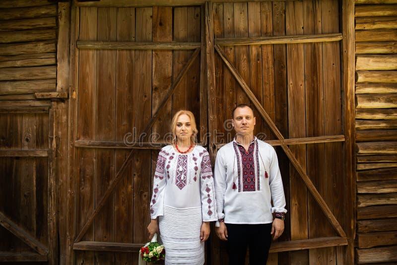 Etnisch huwelijk in nationale kostuums Oekraïense huwelijksbruid en bruidegom die zich op de achtergrond van een houten muur bevi royalty-vrije stock afbeeldingen