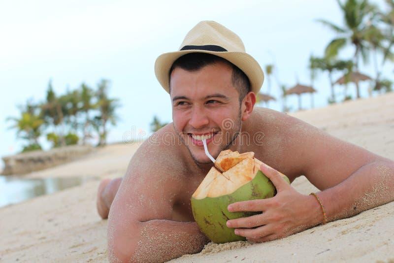 Etnisch mannetje die een verse kokosnoot drinken bij het strand stock fotografie