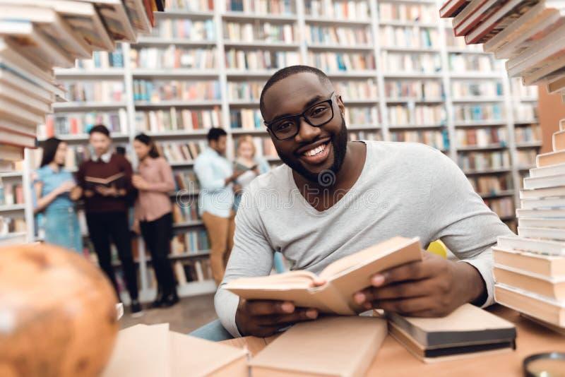 Etnische Afrikaanse Amerikaanse die kerel door boeken in bibliotheek wordt omringd De student leest boek stock foto's