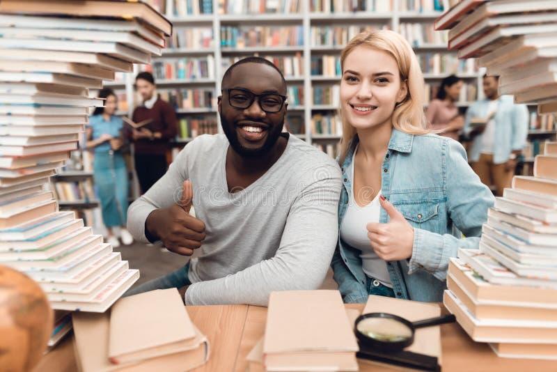 Etnische Afrikaanse Amerikaanse kerel en wit die meisje door boeken in bibliotheek wordt omringd De studenten geven duimen op royalty-vrije stock foto