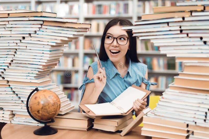 Etnische Aziatische die meisjeszitting bij lijst door boeken in bibliotheek wordt omringd De student schrijft in notitieboekje royalty-vrije stock fotografie
