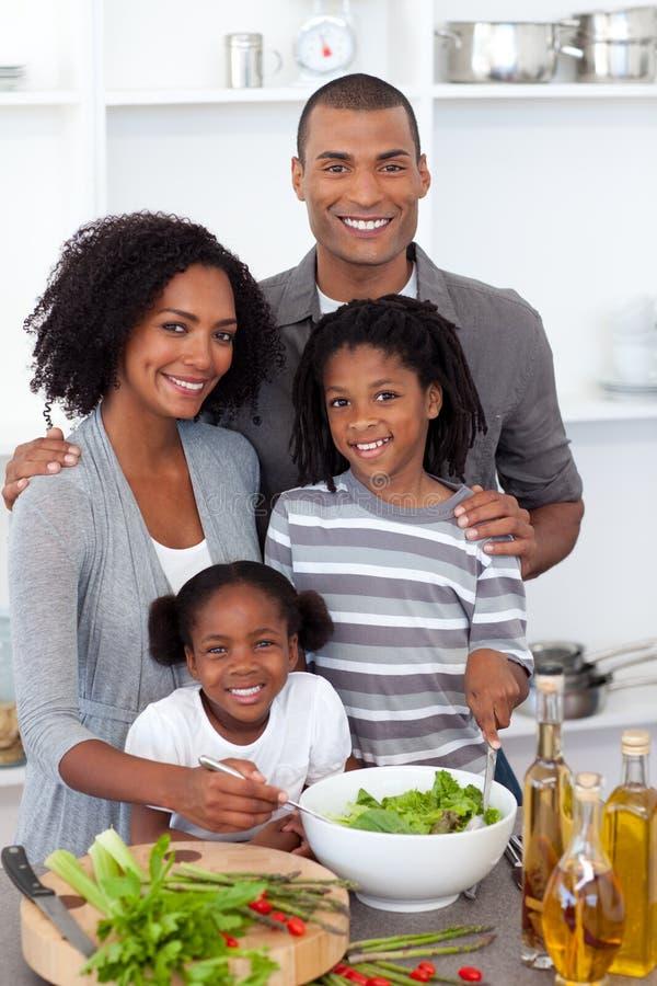 Etnische familie die salade samen voorbereidt stock afbeelding