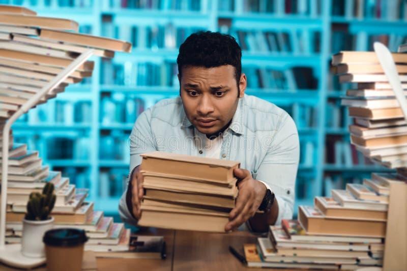 Etnische Indische gemengde die raskerel door boeken in bibliotheek wordt omringd De student houdt boeken stock fotografie