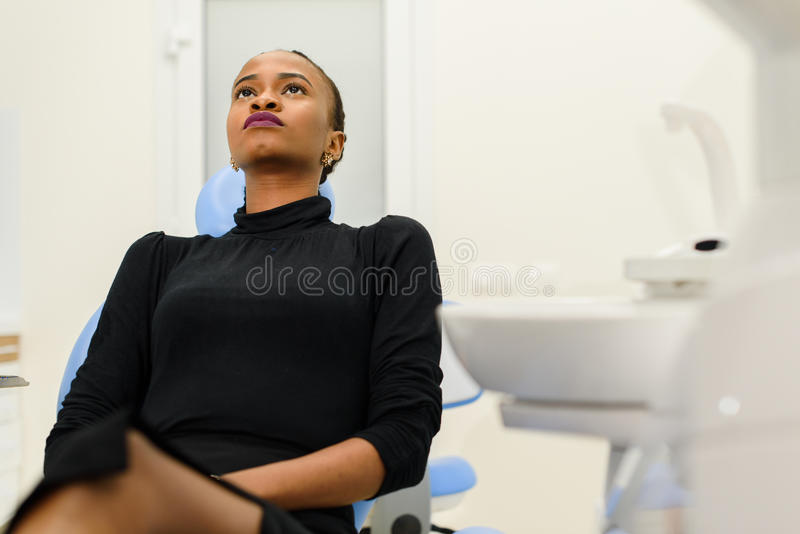 Etnische zwarte vrouwelijke geduldige zitting die omhoog op tandstoel kijken die op haar tandarts wachten stock foto