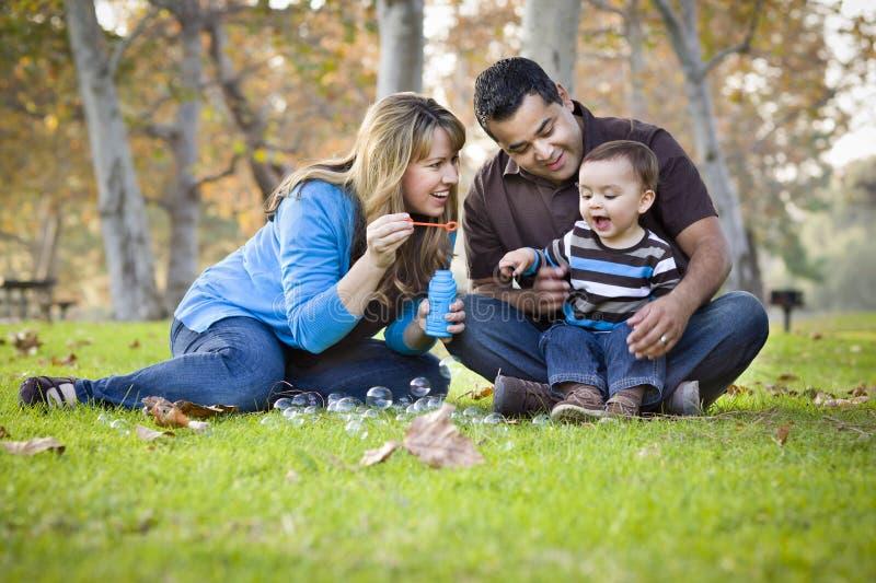 Etnisk familj för blandad Race som leker med bubblor arkivbilder