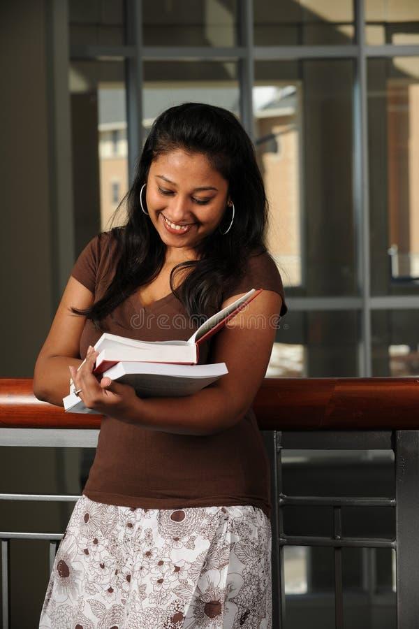 Etnisk högskolestudentläsebok royaltyfri fotografi