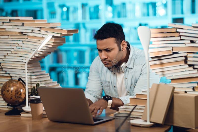 Etnisk indisk grabb för blandat lopp som omges av böcker i arkiv Studenten använder bärbara datorn arkivfoton