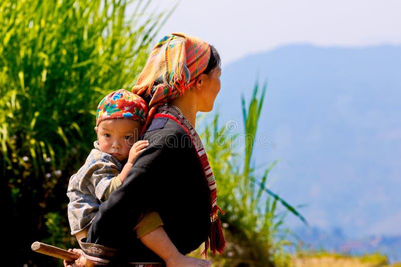Etnisk mamma och hennes barn på berget nära att mogna risterrasser arkivbild
