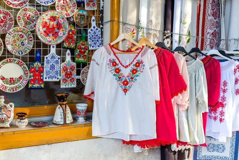 Etniska skjortor med traditionell ungersk broderi och dekorativa målade plattor och skärbrädor i ett gatalager royaltyfri bild