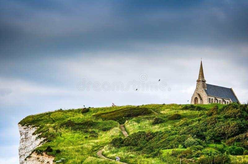 Etretat,法国- 2012年6月29日 峭壁的教会英吉利海峡在有自然曲拱的诺曼底 免版税库存图片