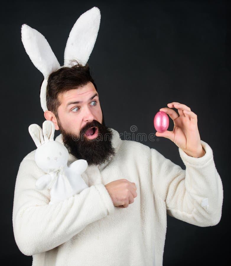 Ett ägg är mest kär på easter Symboler av våren, nytt liv och fertilitet Hipster med kaninöron som rymmer kaninleksaken och royaltyfria foton