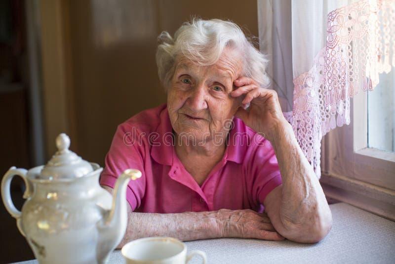 Ett äldre kvinnasammanträde i köket Stående fotografering för bildbyråer