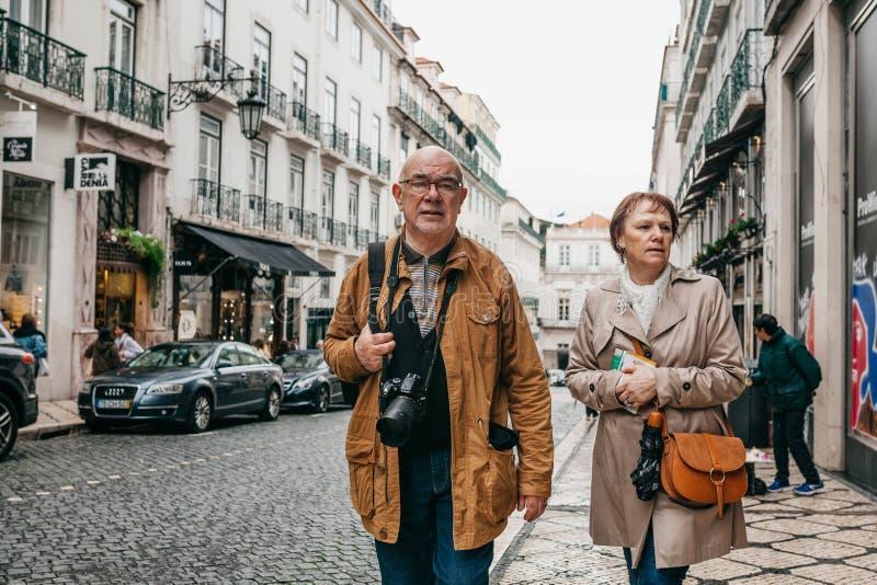 Ett äldre par av europeiska turister går runt om Lissabon i Portugal arkivbild