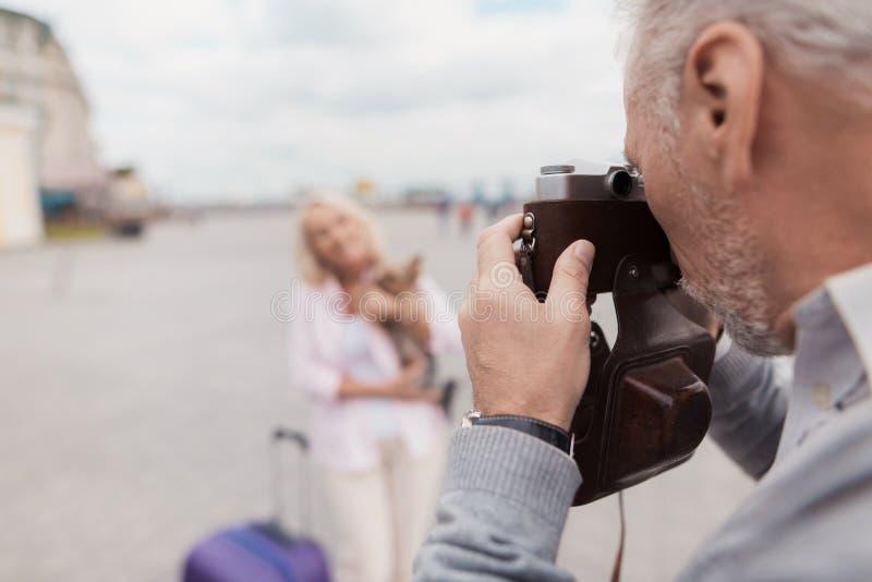 Ett äldre par går En kvinna poserar med en hund i hennes armar, en man tar bilder av henne på en filmkamera royaltyfri fotografi