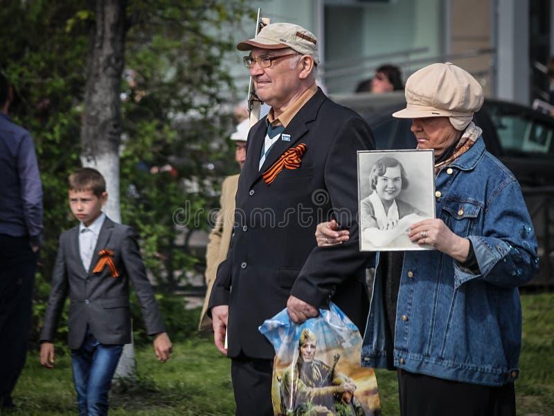Ett äldre par med en stående av ett relativt tagande särar i det odödliga regementet på 9 Maj, 2016 i Ulyanovsk, Ryssland arkivfoton