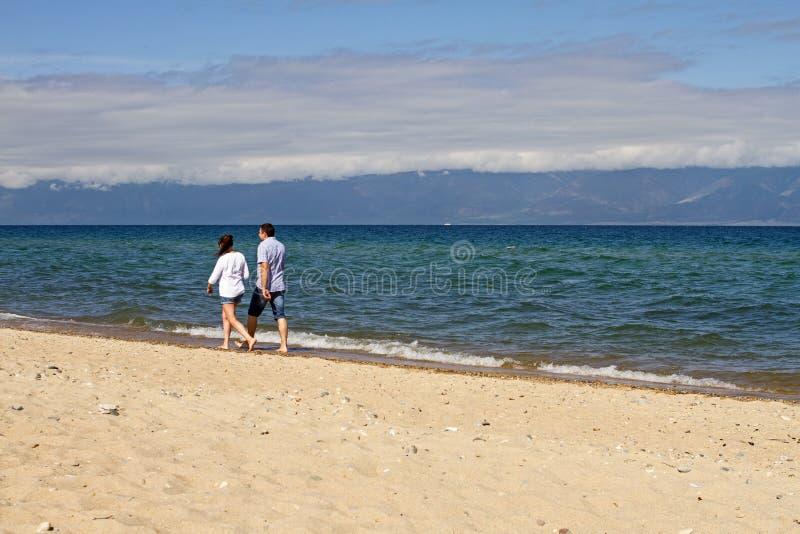 Ett älska par av en man och en kvinna promenerar sandkustlinjen av Lake Baikal på en bergbakgrund på en solig dag royaltyfri bild