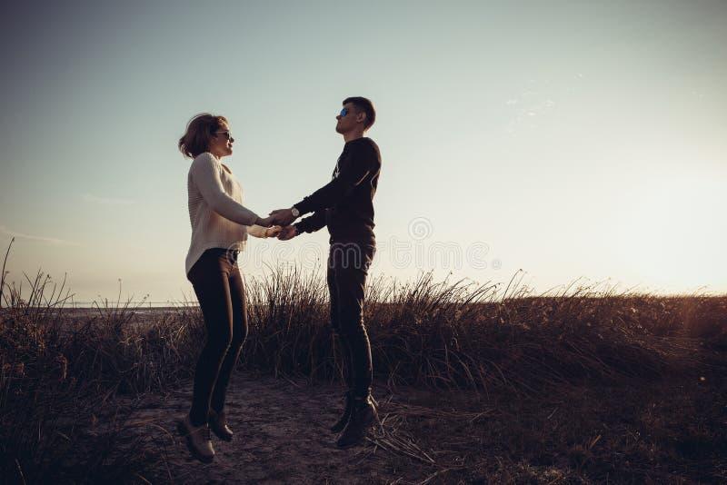 Ett älska par av tonåringar som hoppar upp innehavhänder arkivfoto