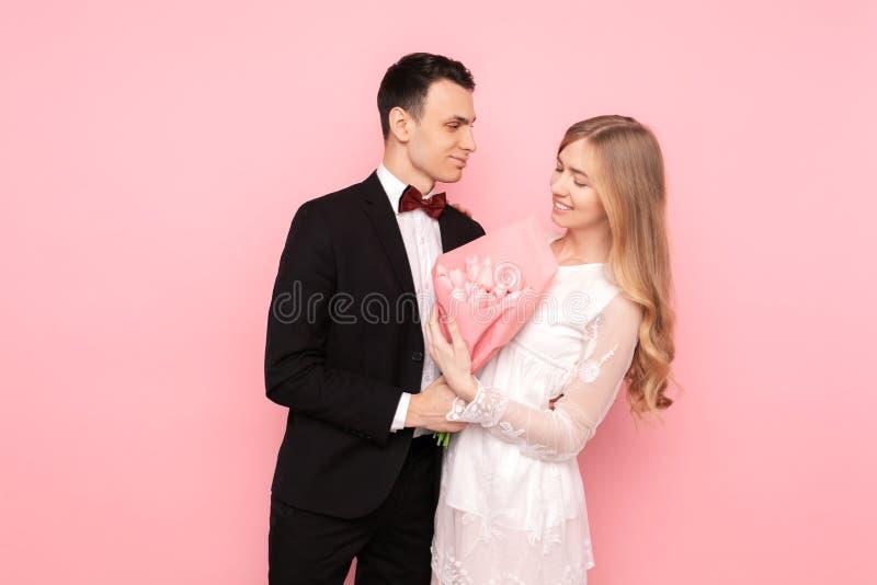Ett älska par, en man ger en kvinna en bukett av tulpan, på en rosa bakgrund Begrepp för dag för valentin` s royaltyfri foto