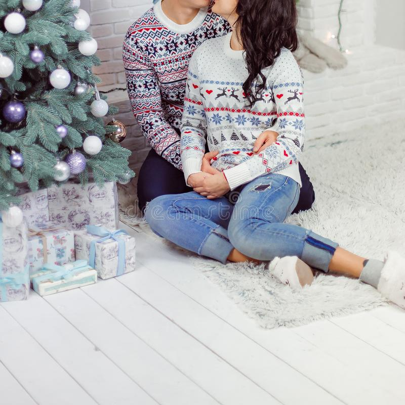Ett älska par sitter på golvet nära trädet för det nya året royaltyfria bilder