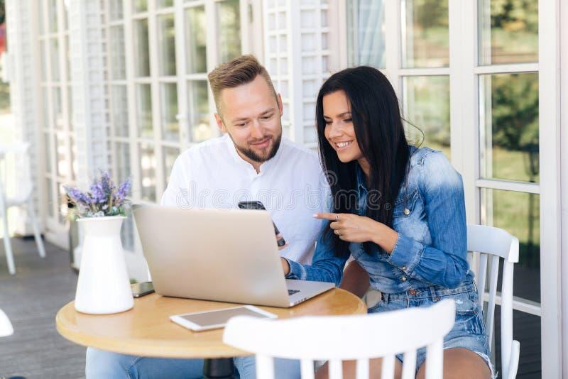 Ett älska par sitter utanför på en tabell i ett kafé och diskuterar en film som ser bärbara datorn par skissar arkivfoton