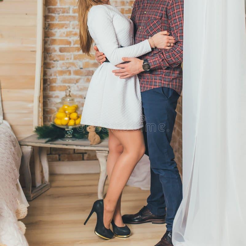 Ett älska par står på kramarna för fönstret och för en man en kvinna arkivbilder