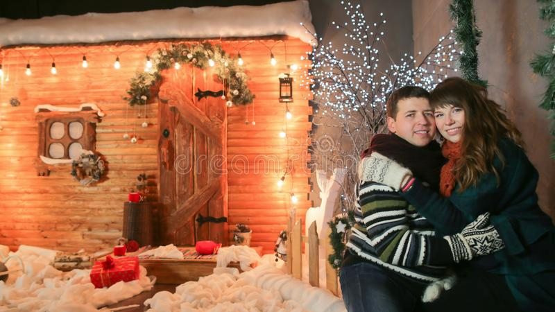 Ett älska par tycker sig om mot en bakgrund av sagagarneringar Tema för jul och för nytt år arkivfoto