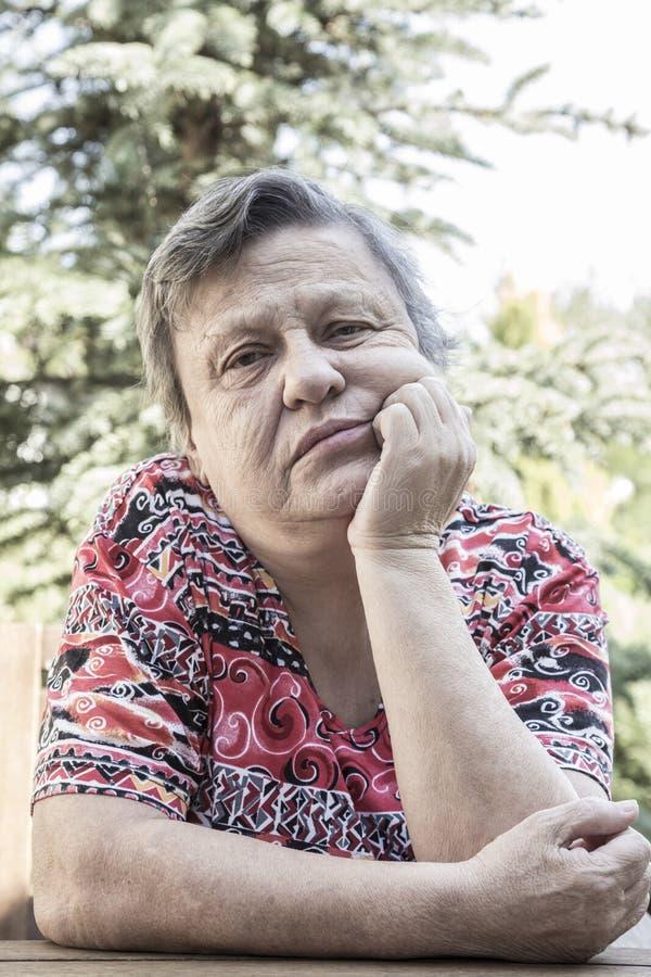 Ett älskvärt sammanträde för gammal kvinna på trädgården royaltyfri bild