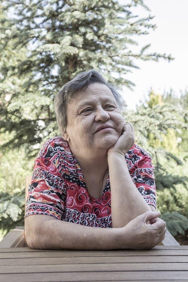 Ett älskvärt sammanträde för gammal kvinna på trädgården royaltyfri fotografi