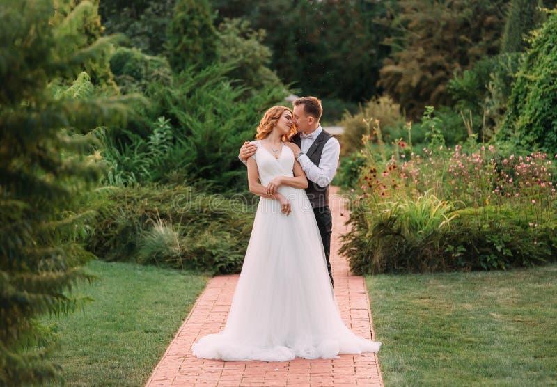 Ett älskvärt ungt par, en brud i en lång ljus vit bröllopsklänning och en brudgum i en ursnygg grön trädgård en man arkivfoton