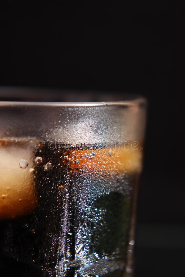Ett ånga exponeringsglas av den kalla törsta-släcka röd-brunt drinken med iskuber fotografering för bildbyråer