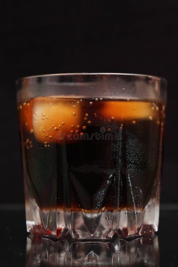 Ett ånga exponeringsglas av den kalla törsta-släcka röd-brunt drinken med iskuber arkivbilder