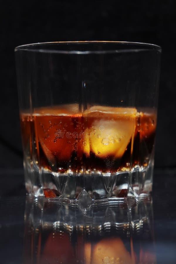 Ett ånga exponeringsglas av den kalla törsta-släcka röd-brunt drinken med iskuber arkivbild
