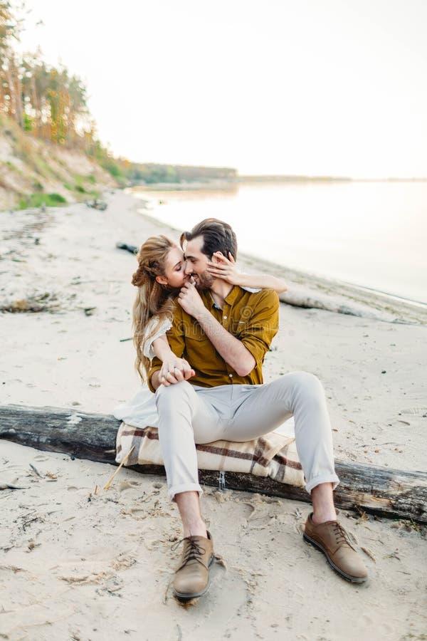 Ett ögonblick för en kyss Barnparet har roligt och kramar på stranden Den härliga flickan omfamnar hennes pojkvän från royaltyfri foto