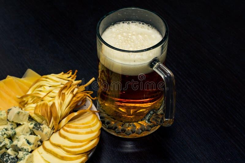 Ett öl rånar och en platta med flera sorter av ost fotografering för bildbyråer