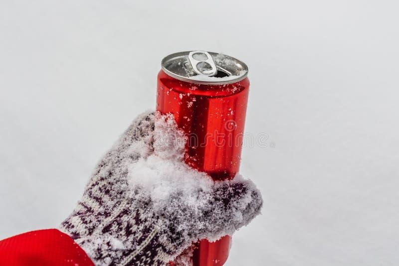 Ett öppnat rött skinande ljust tenn kan med vit snö på dess yttersida med tangenten för kalla kalla läsk i en hand i a royaltyfri fotografi