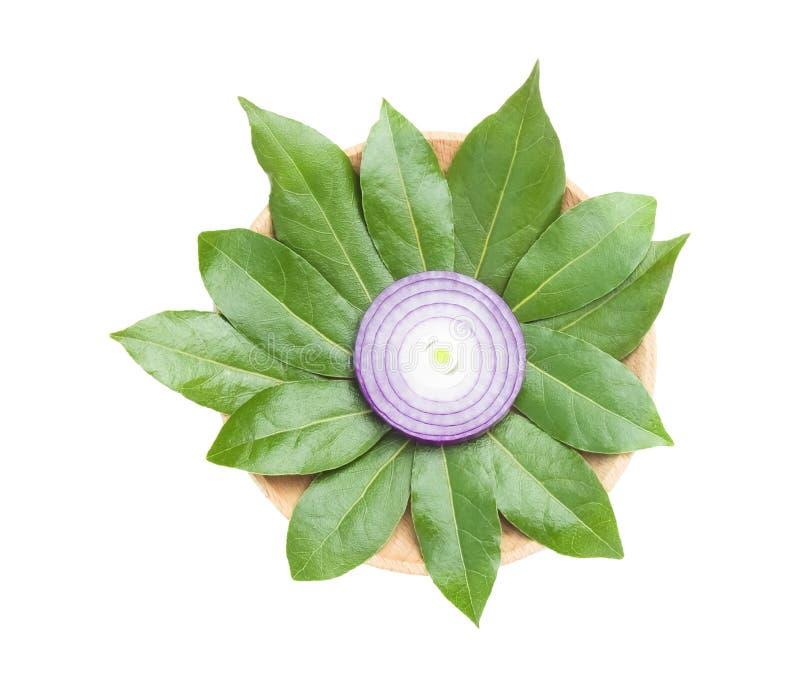 Ett över huvudet foto av den skivade purpurfärgade löken och lagerbladar som en blomma som isoleras på vit Top beskådar Lagersido royaltyfria foton