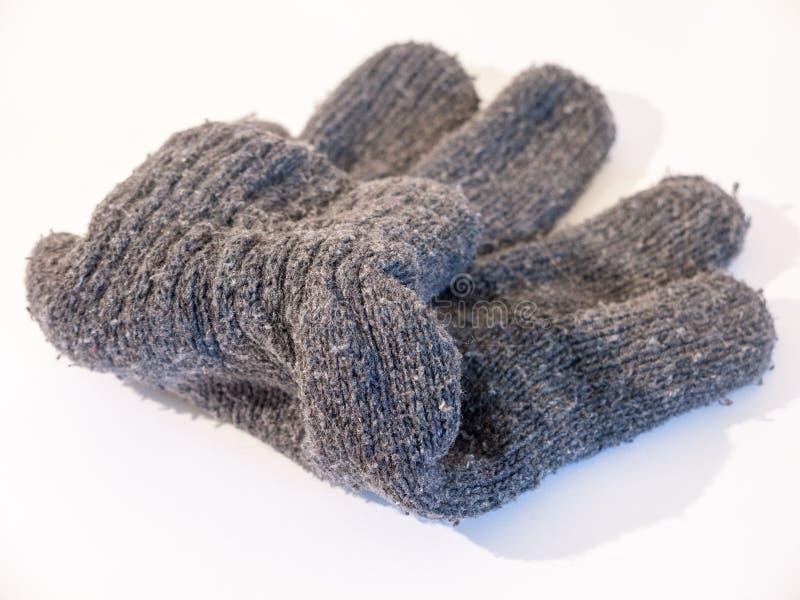 Ett övre materielfoto för slut av en grå handske som används för händer i vinter arkivbild