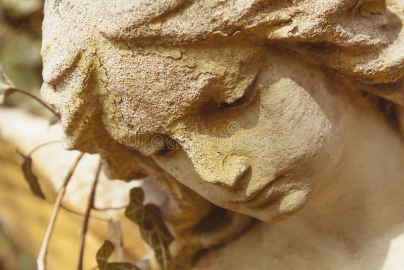 Ett abstrakt foto av en forntida staty fragment Den ledsna ängeln ser från himlen till mänsklighet arkivbilder