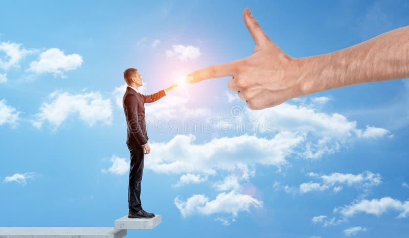 Ett affärsmananseende bland molnen som trycker på fingrar med en jätte- hand arkivfoton