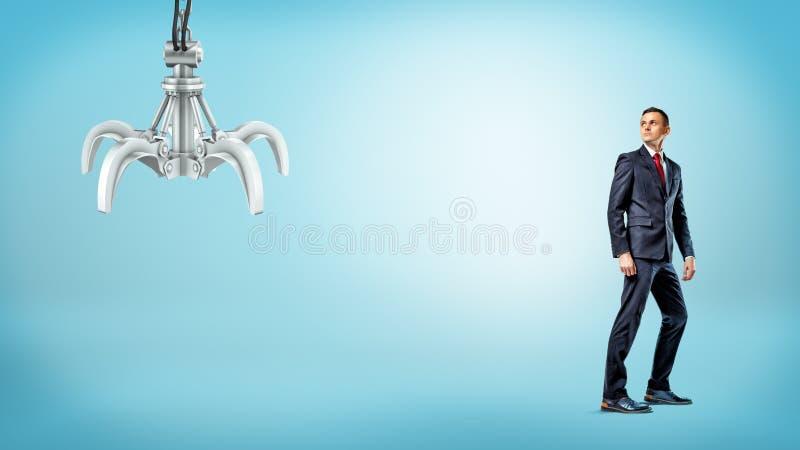 Ett affärsmananseende på blå bakgrund halva-vände för att se en metallisk robotic hand royaltyfri bild