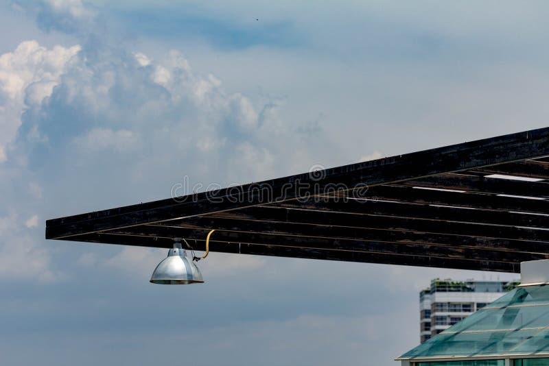 Ett aluminiumljus på en svart träspaljé royaltyfri fotografi