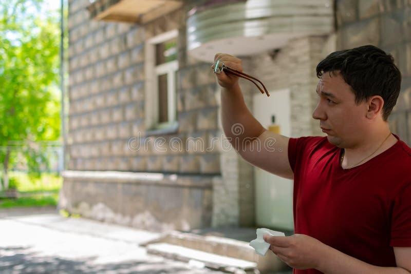 Ett anseende för ung man på gatan med fattiga ögon gnider hans exponeringsglas med en servett arkivfoton