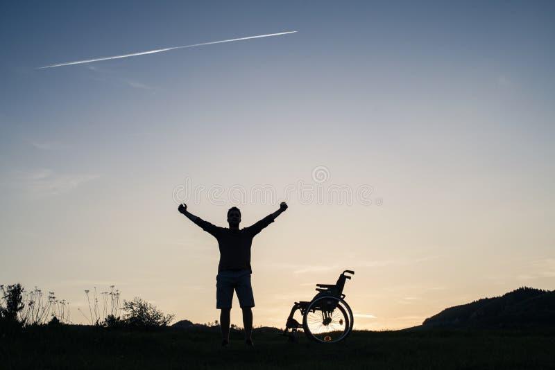 Ett anseende för ung man vid rullstolen i natur i aftonen arkivfoto
