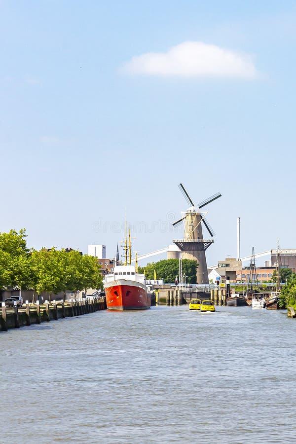 Ett anslutit lastfartyg, vattentaxi och i bakgrunden vindhavren maler 'De Distilleerketel 'i Delfshaven arkivfoton