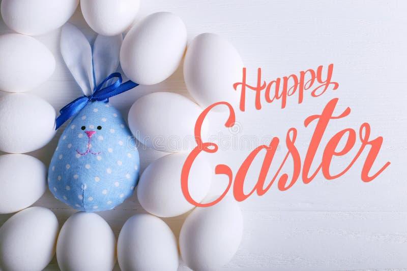 Ett antal ägg, inklusive den handgjorda påskkaninen Text lyckliga easter royaltyfria bilder
