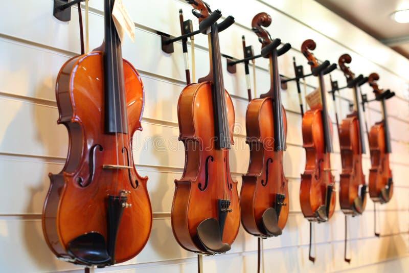 Ett antal fioler som hänger på väggen royaltyfri foto