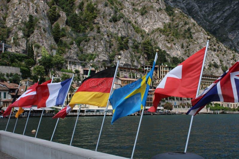 Ett antal flaggor i linje över Garda sjön med kusten i den tillbaka jordningen arkivbilder